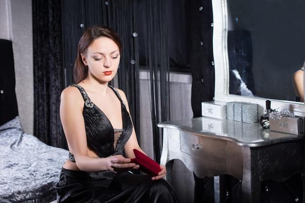 Крупным планом великолепная молодая женщина в сексуальном элегантном платье сидит в своей комнате во время ожидания
