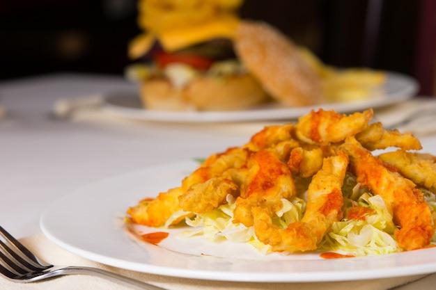 야채에 미식가 튀긴 생선 고기를 닫습니다. 레스토랑의 화이트 플레이트에 제공됩니다.