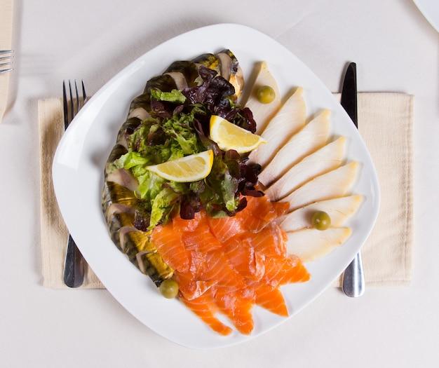 Закройте вверх по изысканному аппетитному мясному основному блюду с овощами и ломтиками лимона на белой круглой тарелке. размещено на белом столе для обеда.