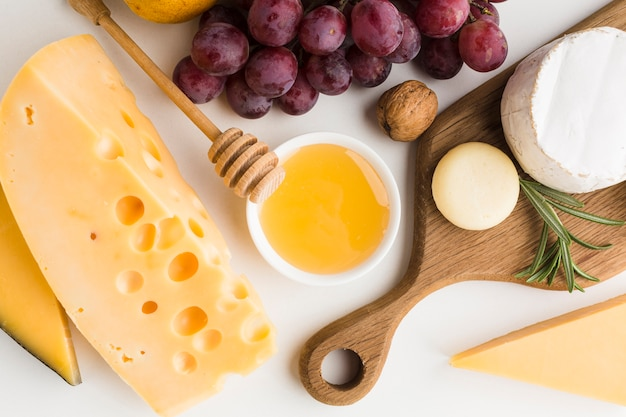 Close-up gourmet assortment of cheese on wooden cutting board and grapes