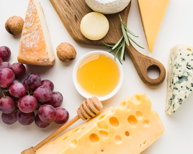 Close-up gourmet assortment of cheese on wooden cutting board honey and grapes