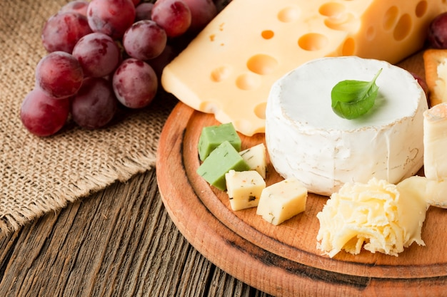Close up gourmet cheese assortment on wooden cutting board with grapes