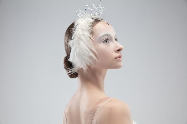 Primo piano di graziosa ballerina classica su sfondo bianco.