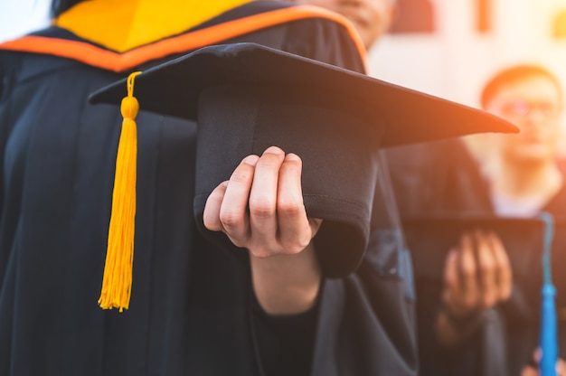 Close up of graduates holding hats in hand Premium Photo