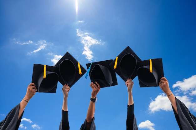 Close up of graduates holding hats in hand