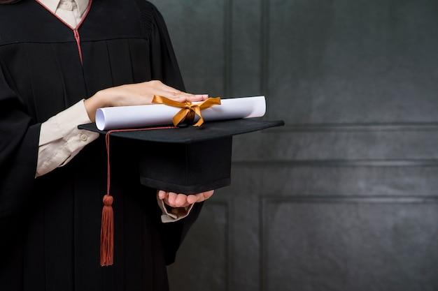 Крупным планом выпускной женщина держит шапку и сертификат