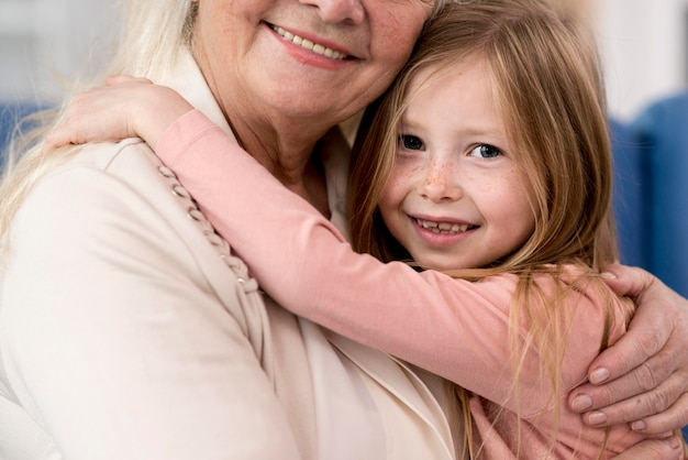 Close-up grandma and girl hugging