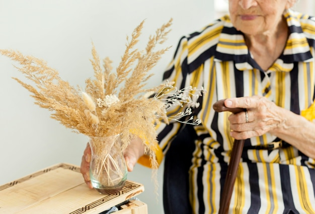 Close-up grandmother holding flowers