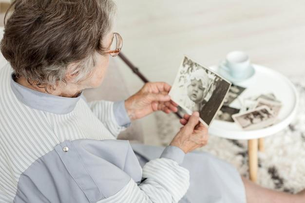 Макро бабушка смотрит на старые фотографии