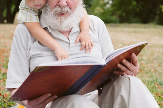 Close-up grandpa and grandson reading