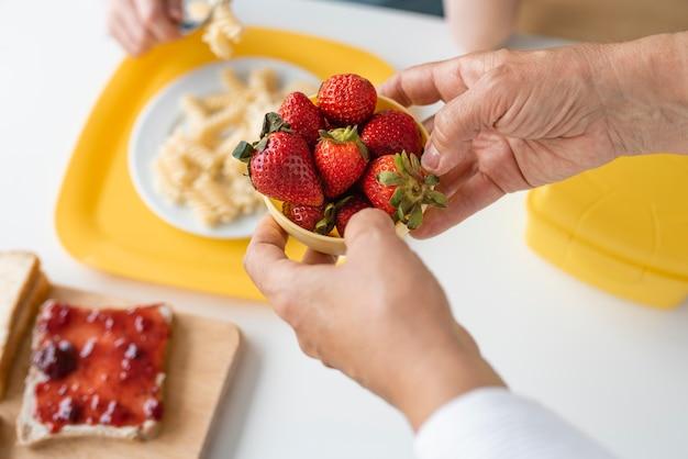 Close up grandparent holding strawberries bowl