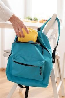 Close up grandparent preparing backpack
