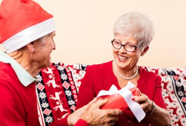 Close-up of grandparents giving christmas presents