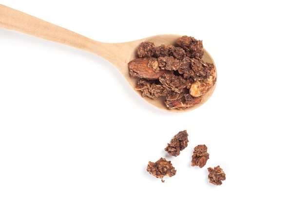 Close up granola on the wooden spoon isolated on white background.