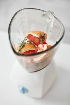 Close up of grapefruit pieces and rosemary in blender. healthy fitness diet nutrition.