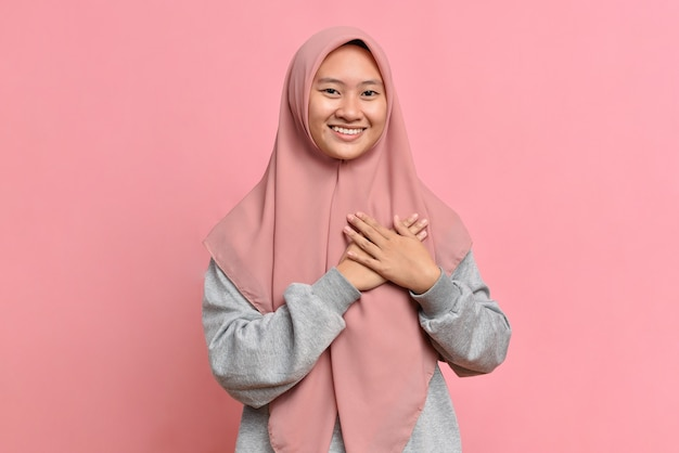 Close-up grateful, muslim asian woman feeling touched and flattered, smiling and gazing with affection, touch heart, express gratitude and delight of receiving nice gift, isolated on pink background