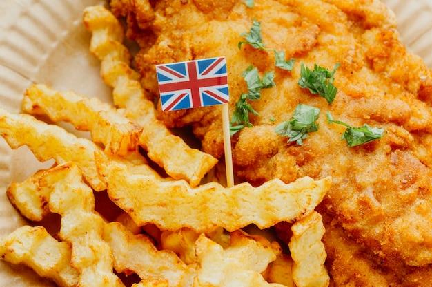 Primo piano della bandiera della gran bretagna nel piatto di pesce e patatine