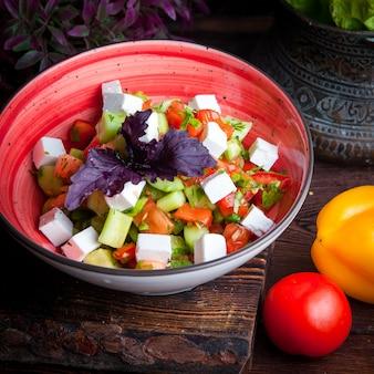Close up greek salad lettuce, tomatoes, feta cheese, cucumbers, black olives, purple onion
