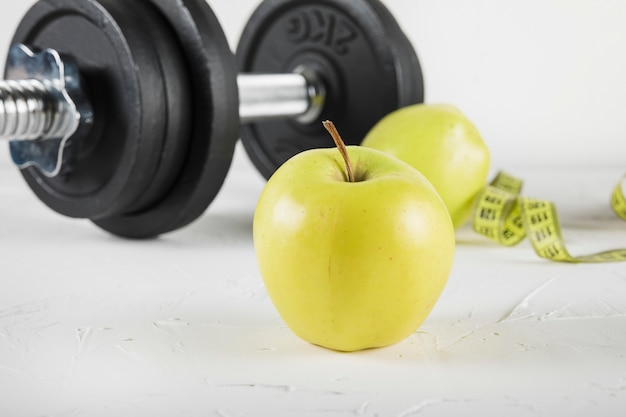 Close-up of green apple and dumbbell on white surface