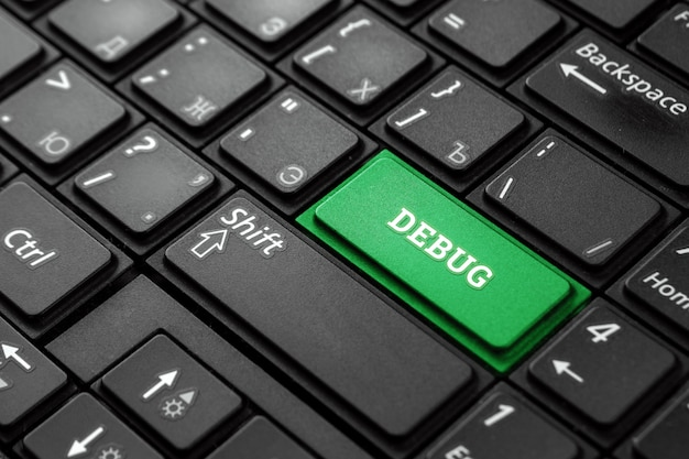 Close-up green button with the word debug, on a black keyboard. creative background, copy space. concept magic button, repair, fix.