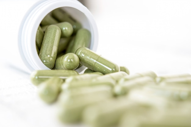 Close up of green capsules herbal medicines spillig out from the bottle