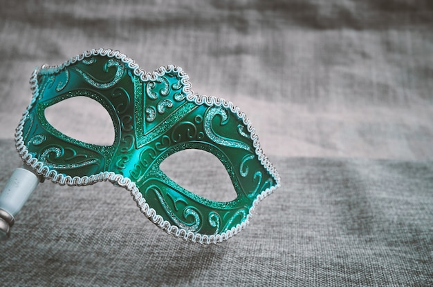 Close up green carnival masquerade, venetian mask place on the burlap texture