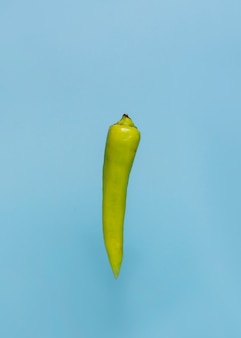 Close-up of a green chili pepper on blue surface
