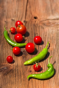 Close-up of green chili peppers and red cherry tomatoes on wooden backdrop