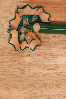 Close-up of green colored pencil with shavings