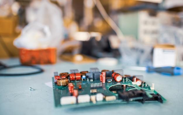 장비 생산을 위해 공장에서 컴퓨터를 추가 생산할 준비를 하기 위해 근접한 녹색 내장 미세 회로가 테스트 플레이트에 쌓여 있습니다.