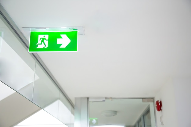 Close up green emergency fire exit sign or fire escape in the building