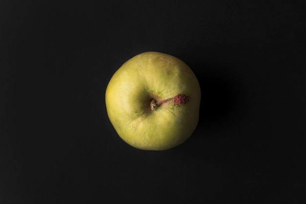 Close up of a green fresh apple isolated over black