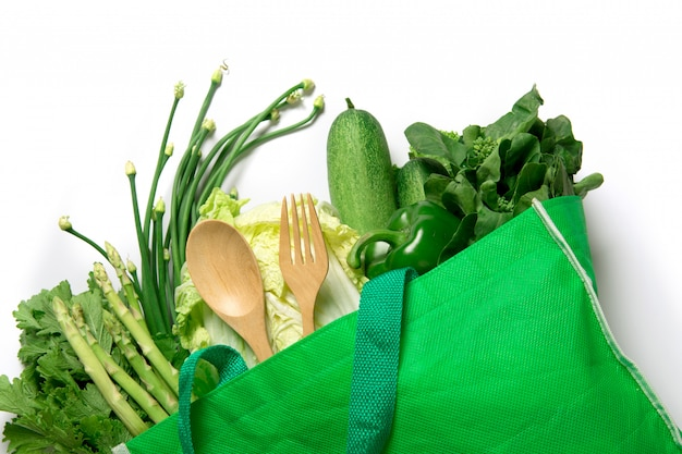 Close up a  green grocery bag of mixed organic green vegetables on white