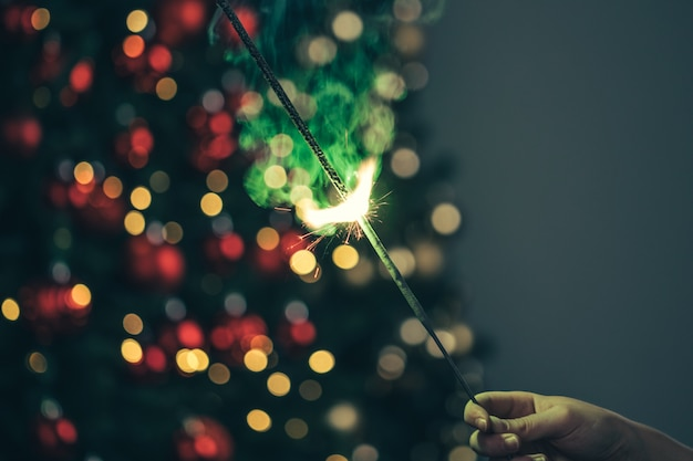 Close-up of green holiday sparkler in the dark