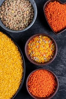 クローズアップの緑、赤、黄色のレンズ豆の異なる色のボウルと黒い石のテーブルに黒い鍋。垂直