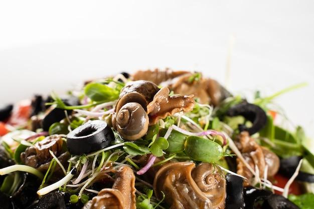 흰색 바탕에 달팽이와 근접 그린 샐러드입니다. 프랑스 미식가 요리.