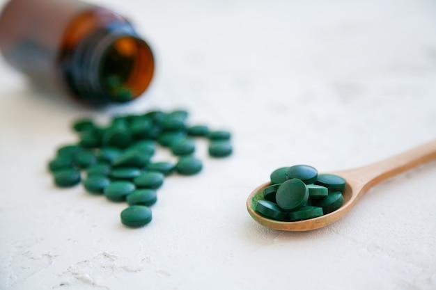 クローズアップの緑のスピルリナの丸薬が白いコンクリートの背景にボトルから落ちた