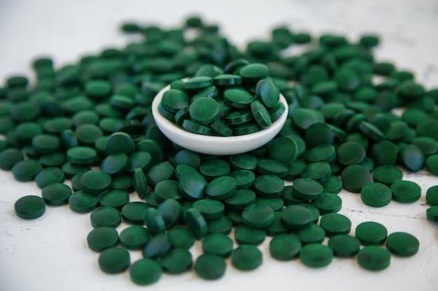 緑のスピルリナの丸薬をクローズアップ。スーパーフードのコンセプト。スピルリナ栄養補助食品。