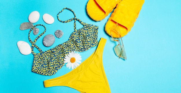 Close-up of green swimsuit, yellow sunglasses and slippers decorated with pebbles and chamomile