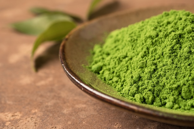 Close up of green tea powder in ceramic dish with leaf on the table.