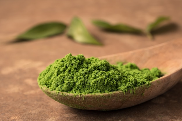 Close up of green tea powder in wooden spoon on the table.