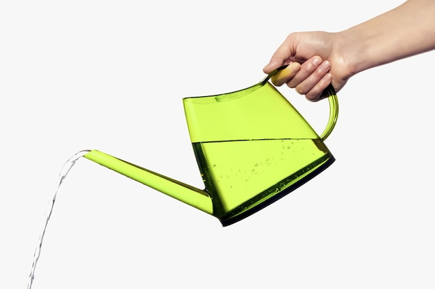 Close up on green watering can held in hand isolated