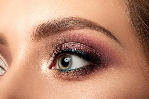 Close up of green woman eye with beautiful brown with red and orange shades smokey eyes makeup modern fashion make up studio shot
