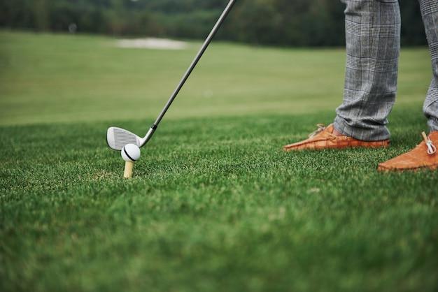 Поле для гольфа зеленой зоны конца-вверх, белый шарик и ручка металла. игрок может видеть только ноги