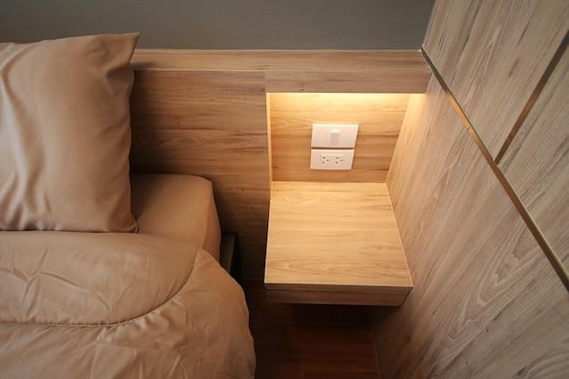 Закройте серую простыню в спальне, уютный интерьер в земных тонах, вид сверху на кровать с деревянным полом