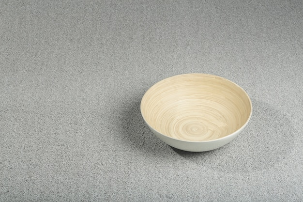Close up on grey carpet texture with wooden bowl