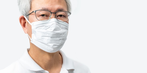 Close up of grey hair asian man's face with glasses wearing white n95 mask