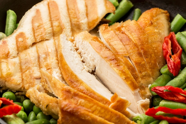 Close-up grilled chicken and peas with chilli peppers