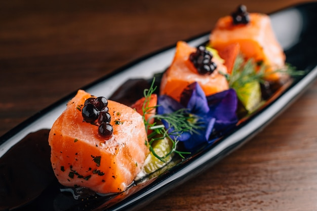 Close up grilled medium rare salmon cube topping with caviar and served with strawberry and orange in black plate.