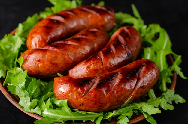 Close up of grilled sausages and arugula on black background.